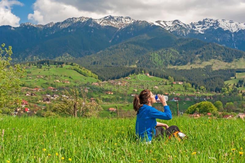 Mujer joven que descansa sobre la colina con paisaje hermoso de la montaña en fondo imagen de archivo