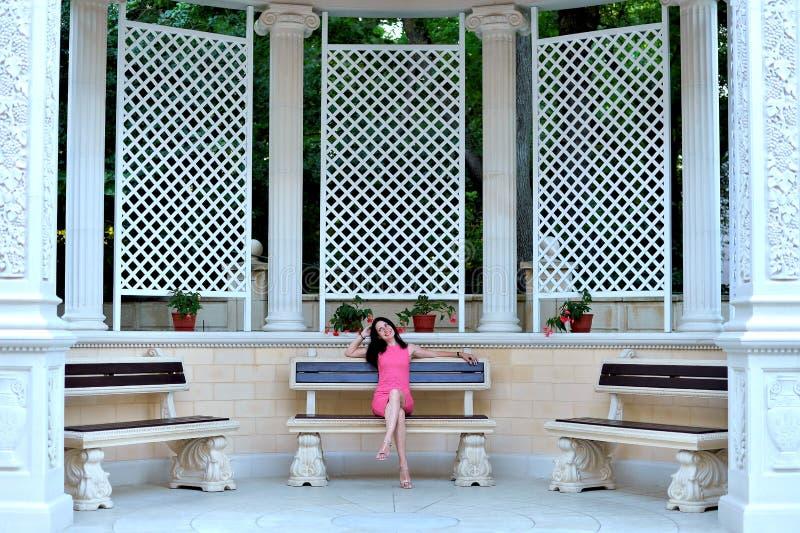 Mujer joven que descansa sobre un banco en un parque hermoso fotos de archivo