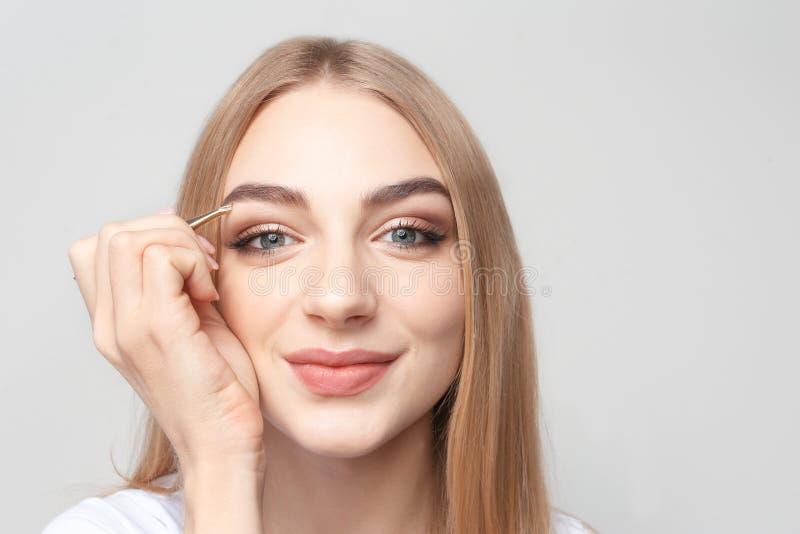 Mujer joven que despluma la ceja con las pinzas foto de archivo