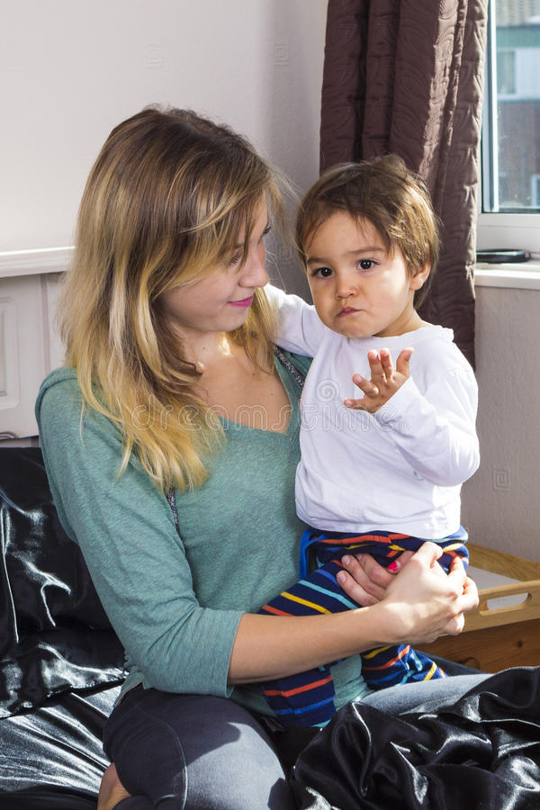 Mujer joven que detiene al hijo en los brazos fotos de archivo libres de regalías