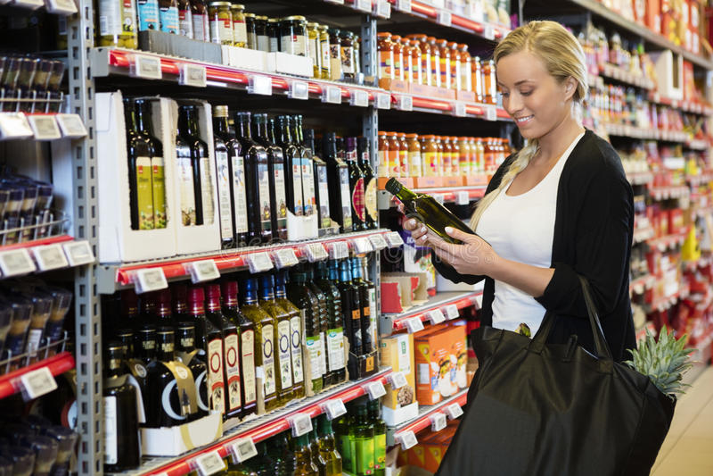 Mujer joven que detiene a Olive Oil Bottle In Supermarket fotografía de archivo
