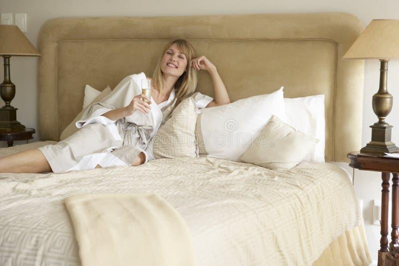 Mujer joven que disfruta de Champán en dormitorio fotografía de archivo libre de regalías