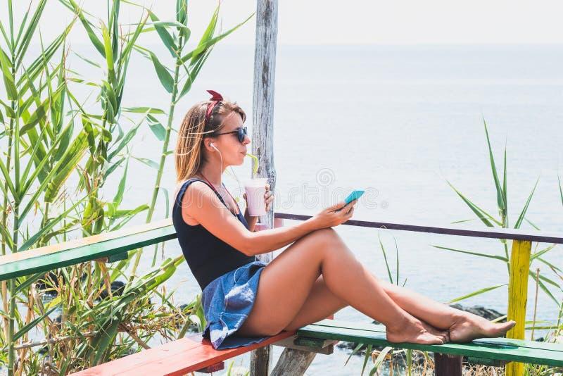 Mujer joven que disfruta de la bebida fría en una barra de la playa fotos de archivo libres de regalías