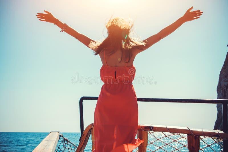 Mujer joven que disfruta de la libertad en un yate de madera El modelo aumentó sus brazos contra el viento imagen de archivo