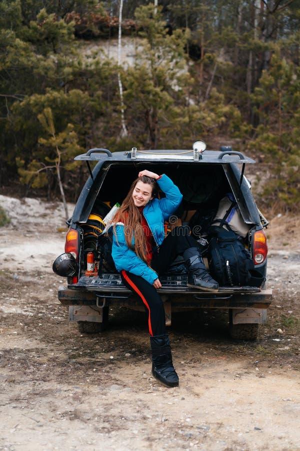 Mujer joven que disfruta de la naturaleza mientras que se sienta en el tronco de coche fotografía de archivo