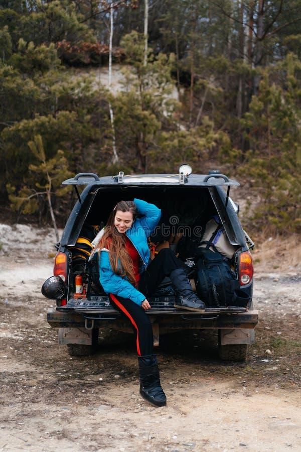 Mujer joven que disfruta de la naturaleza mientras que se sienta en el tronco de coche imágenes de archivo libres de regalías