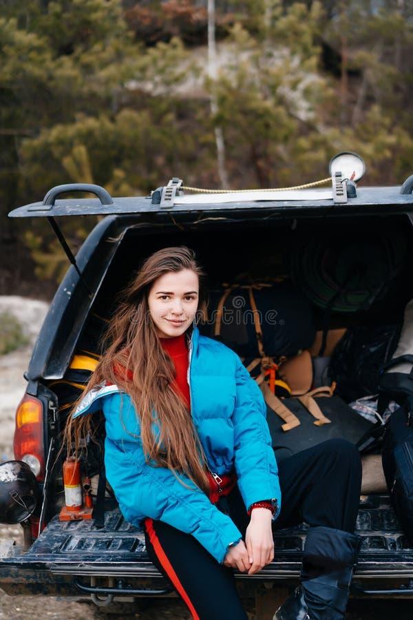 Mujer joven que disfruta de la naturaleza mientras que se sienta en el tronco de coche fotos de archivo libres de regalías