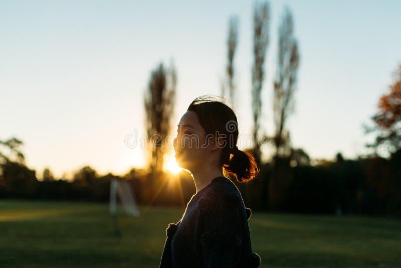 Mujer joven que disfruta de luz del sol en campo de la paja Al aire libre, libertad foto de archivo