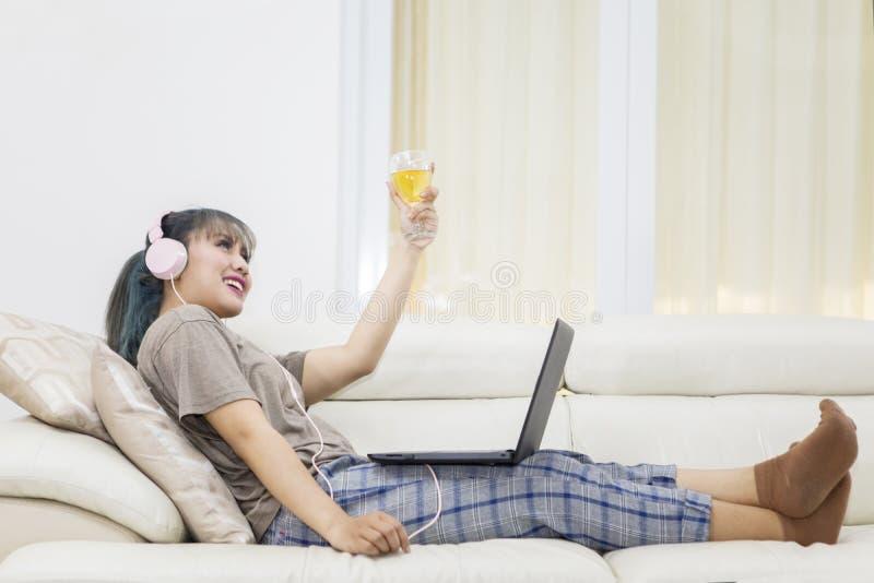 Mujer joven que disfruta de música con champán imagenes de archivo