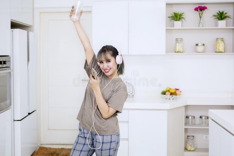 Mujer joven que disfruta de música en la cocina imagen de archivo