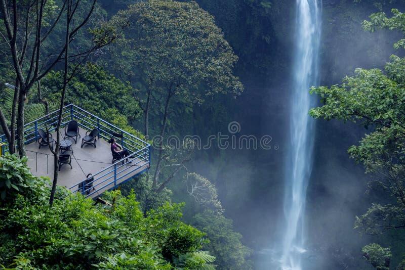 Mujer joven que disfruta de paisaje de la cascada de Pelangi foto de archivo