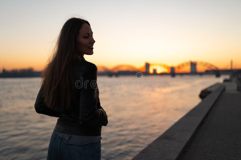 Mujer joven que disfruta de un paseo de la puesta del sol a lo largo del Daugava del río con una visión sobre el cielo azul cla imagen de archivo libre de regalías