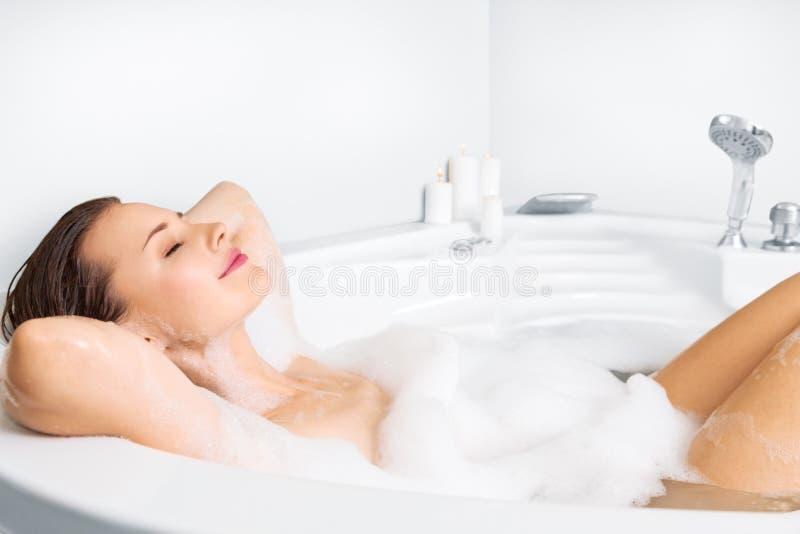 Mujer joven que disfruta del baño en bañera imagenes de archivo