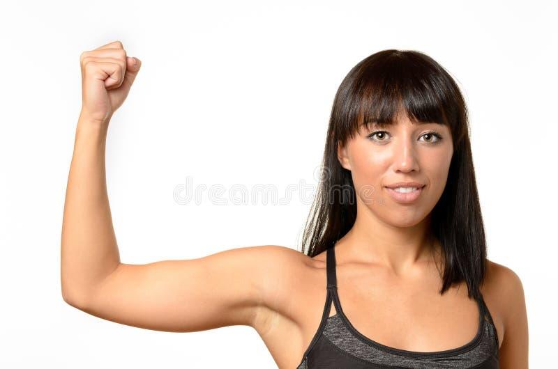 Mujer joven que dobla su brazo para mostrarle el bíceps foto de archivo libre de regalías