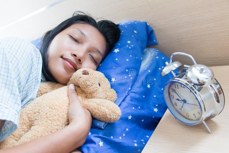 Mujer joven que duerme con el oso de peluche imagenes de archivo