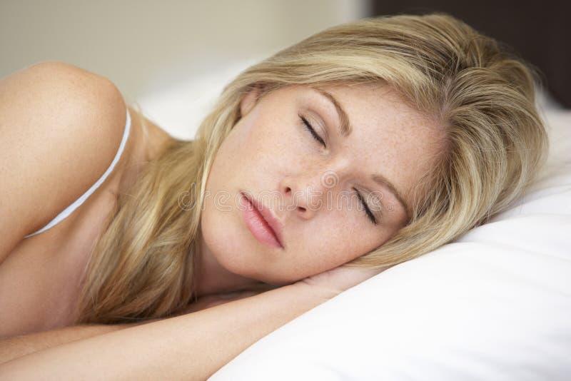 Mujer joven que duerme en cama fotografía de archivo libre de regalías