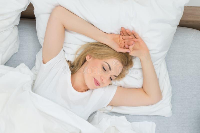 Mujer joven que duerme en cama imagen de archivo