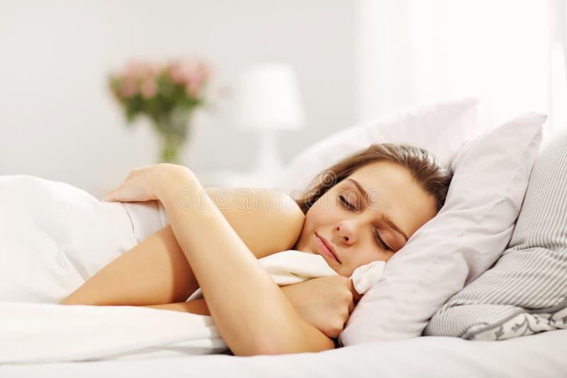Mujer joven que duerme en cama fotos de archivo libres de regalías