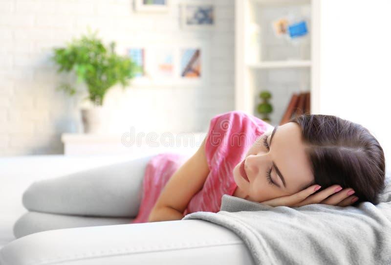 Mujer joven que duerme en el sofá fotografía de archivo libre de regalías