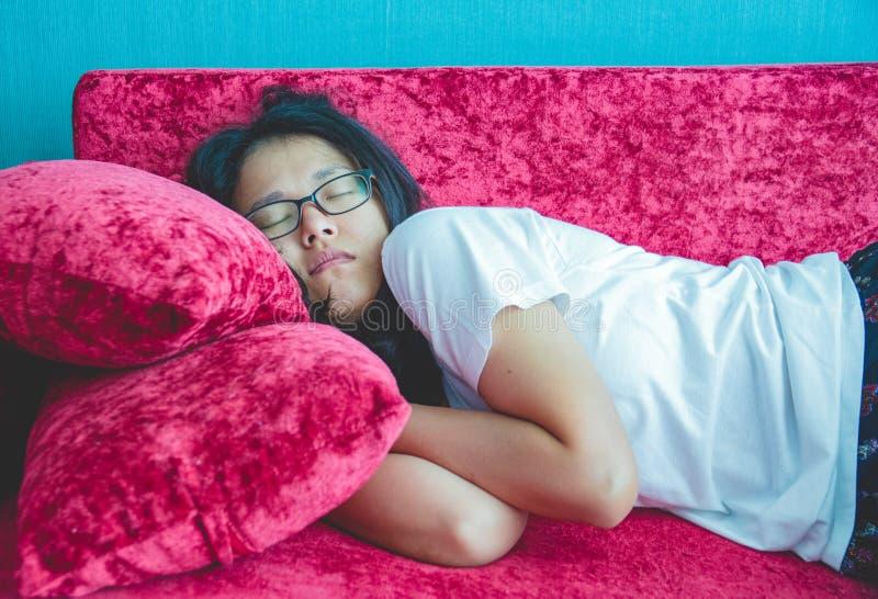 Mujer joven que duerme en el sofá en casa fotografía de archivo
