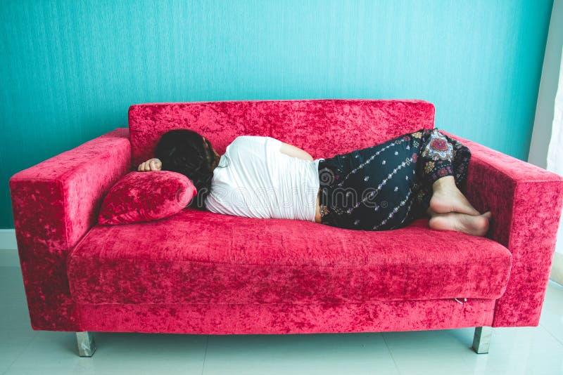 Mujer joven que duerme en el sofá en casa foto de archivo libre de regalías