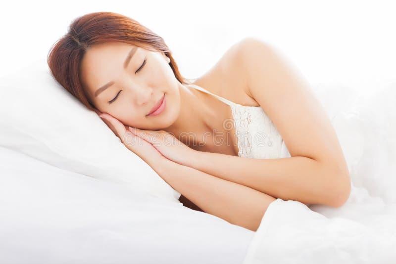 Mujer joven que duerme en la cama fotografía de archivo libre de regalías