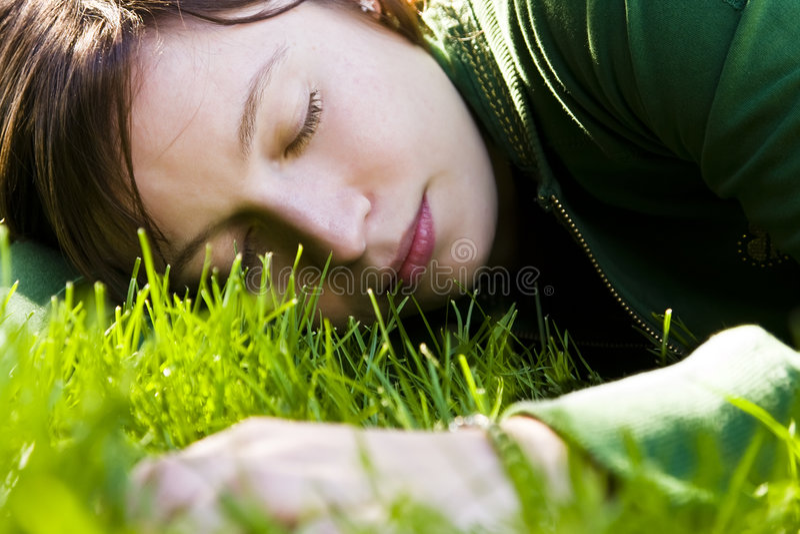 Mujer joven que duerme en la hierba fotos de archivo