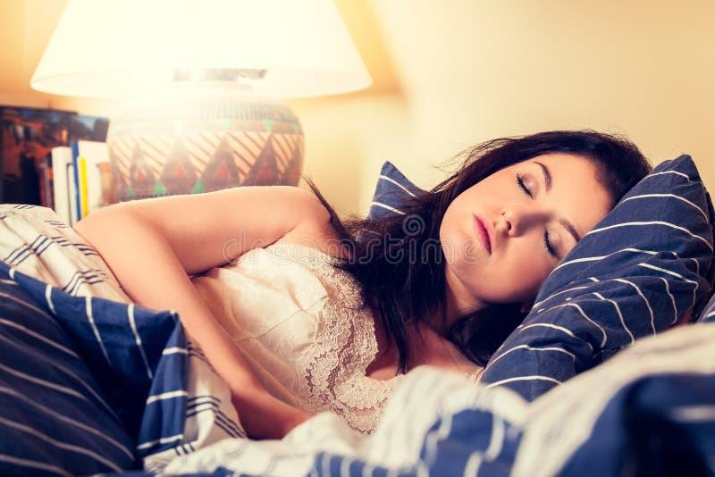 Mujer joven que duerme en las ropas de cama blancas en cama foto de archivo libre de regalías