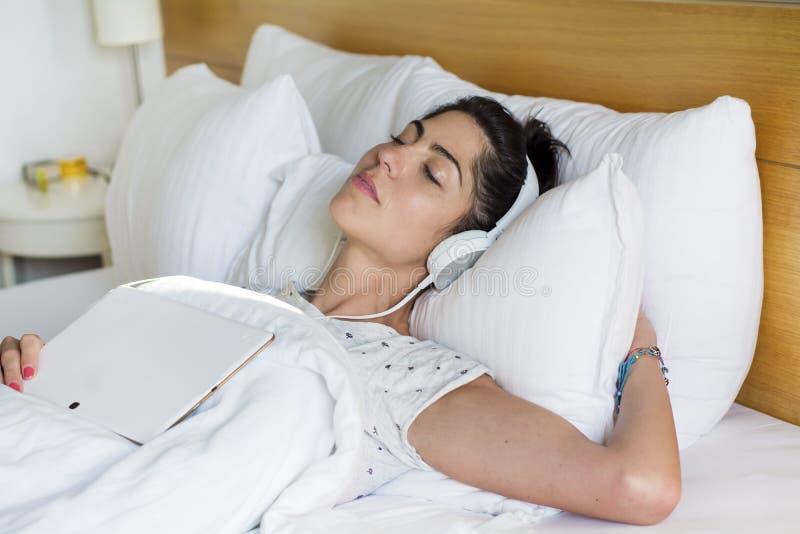 Mujer joven que duerme en música que escucha de la cama foto de archivo