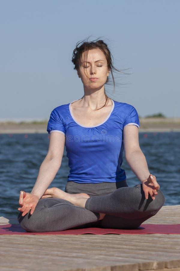 Mujer joven que ejercita actitud de la yoga por la orilla en la puesta del sol, muchacha del lago en actitud de la yoga del heads imagen de archivo libre de regalías