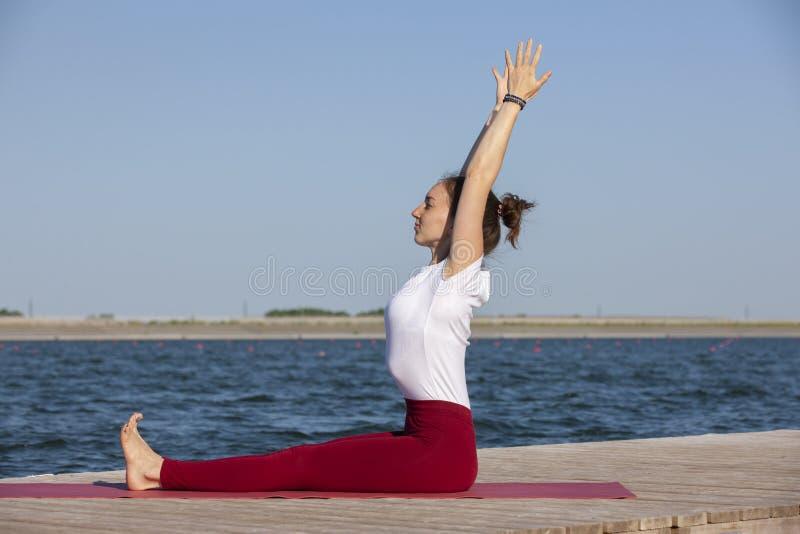 Mujer joven que ejercita actitud de la yoga por la orilla en la puesta del sol, muchacha del lago en actitud de la yoga del heads imagen de archivo