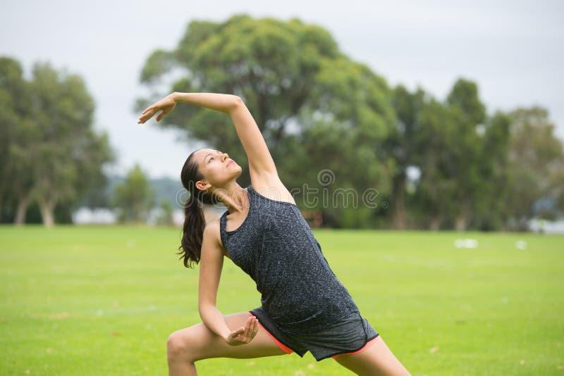 Mujer joven que ejercita aeróbicos en parque imagen de archivo libre de regalías