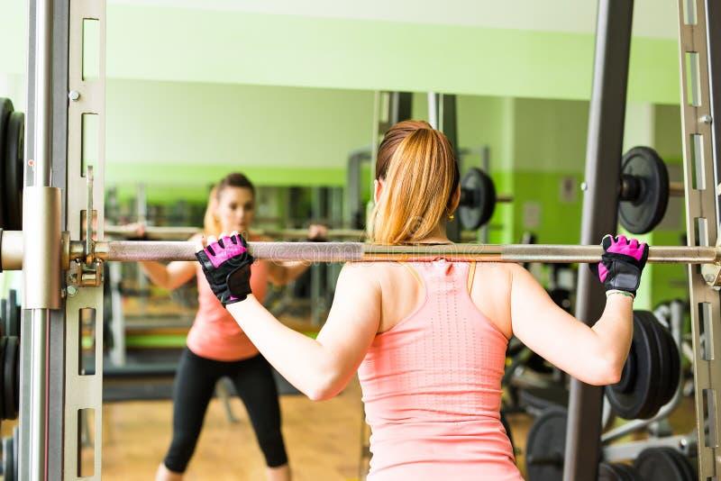Mujer joven que ejercita con el barbell en gimnasio imagen de archivo