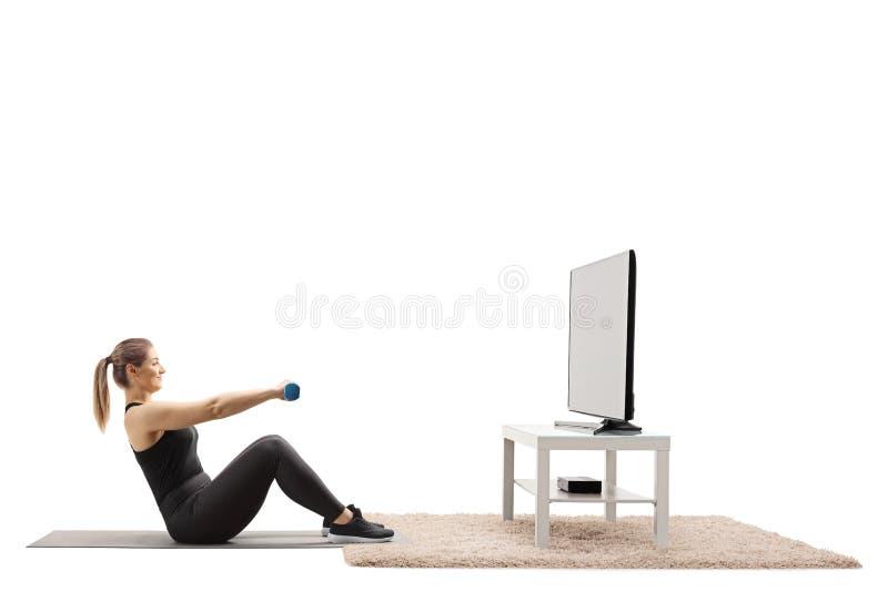 Mujer joven que ejercita con pesas de gimnasia delante de una TV en casa fotos de archivo