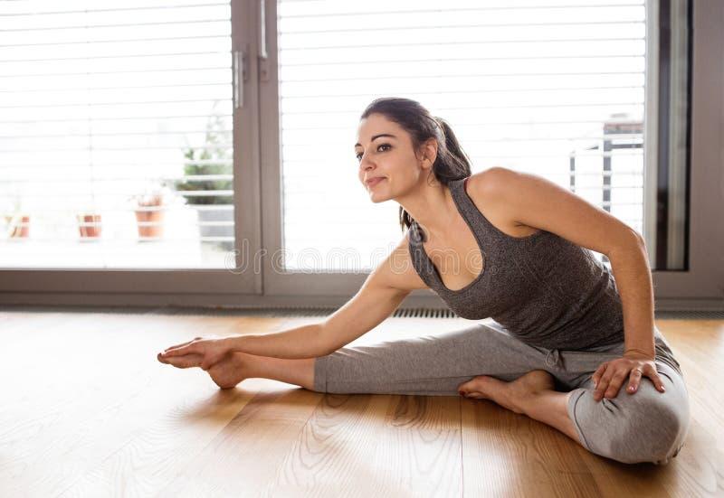 Mujer joven que ejercita en casa, estirando las piernas fotos de archivo