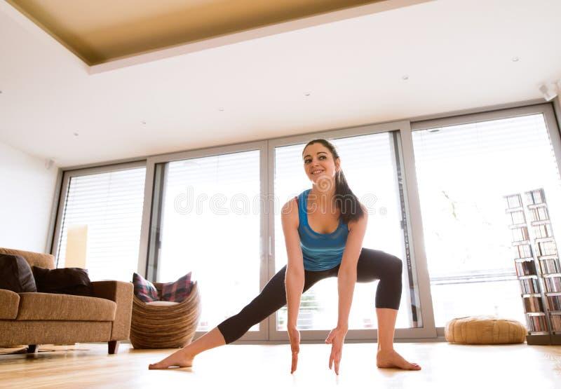 Mujer joven que ejercita en casa, estirando las piernas foto de archivo