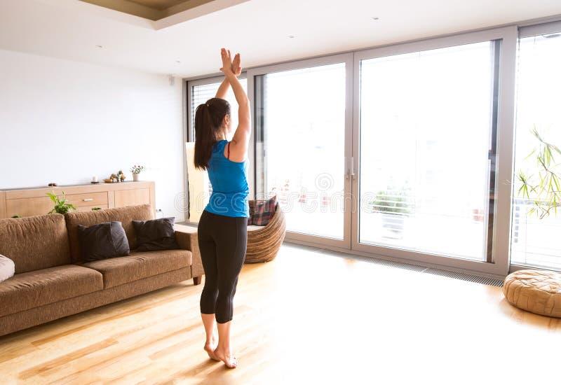 Mujer joven que ejercita en casa, estirando las piernas y los brazos imagen de archivo