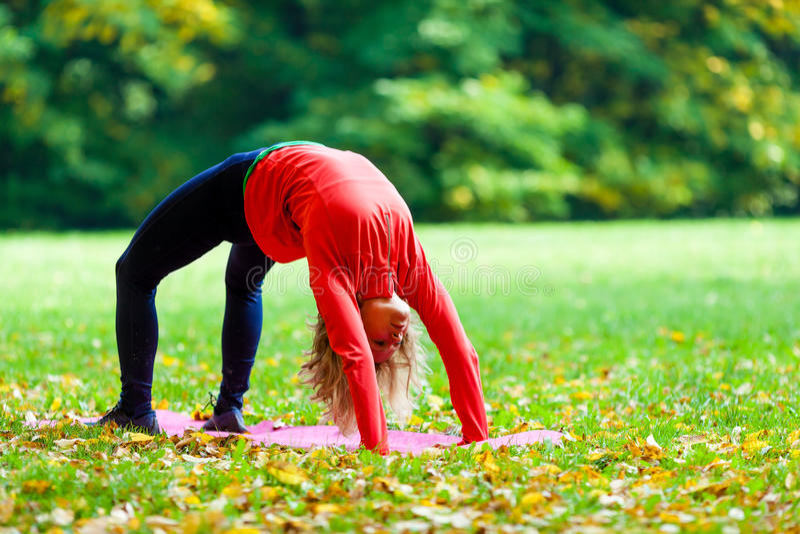 Mujer joven que ejercita otoño de la yoga fotos de archivo libres de regalías