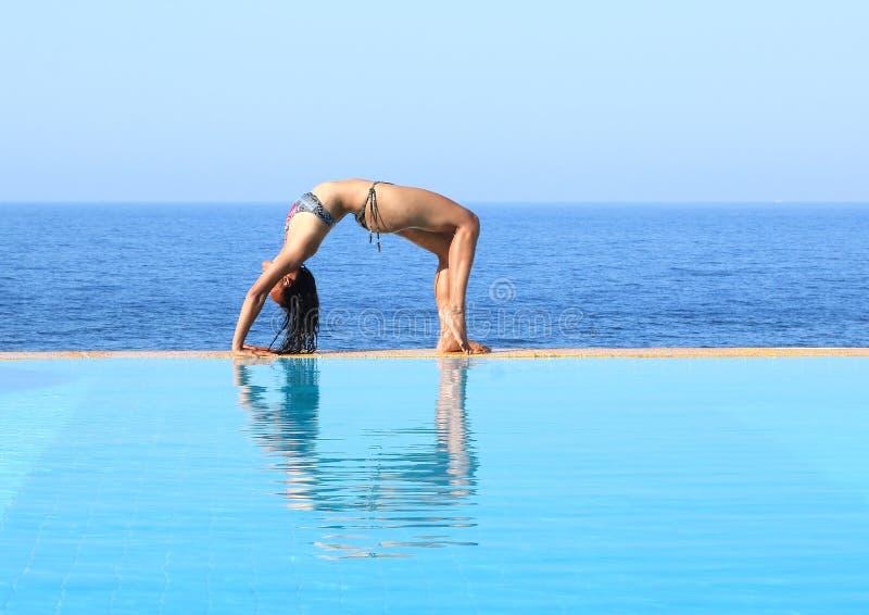 Mujer joven que ejercita yoga en el borde de la piscina por el mar foto de archivo