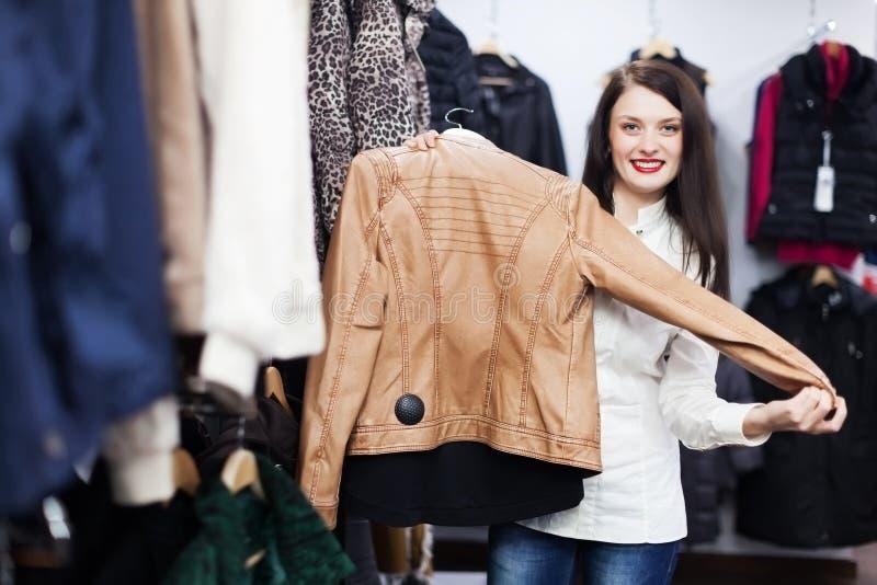 Mujer joven que elige la chaqueta fotografía de archivo libre de regalías
