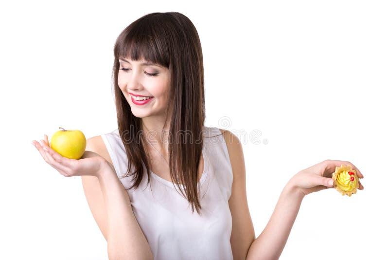 Mujer joven que elige la manzana en vez de la torta imagen de archivo