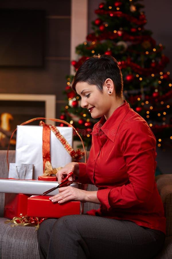 Mujer joven que envuelve los regalos de la Navidad imagen de archivo libre de regalías