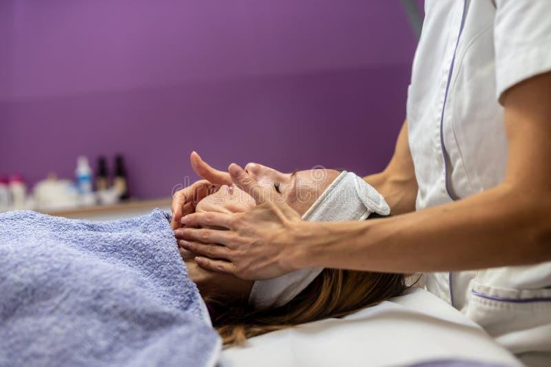 Mujer joven que es cuidada en exceso con masaje facial fotos de archivo