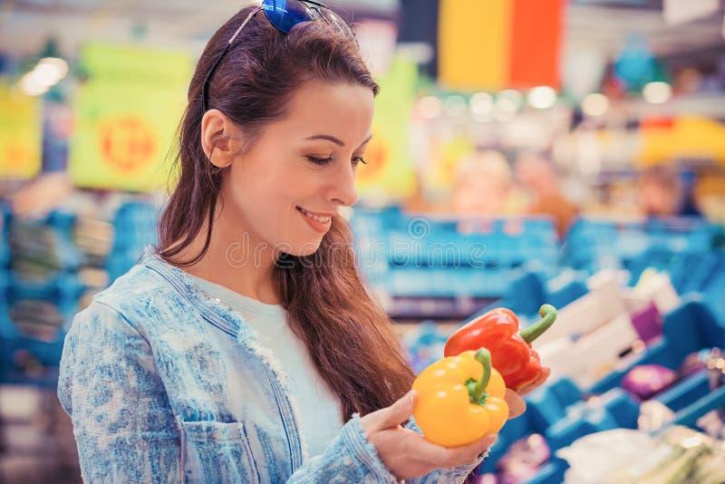 Mujer joven que escoge para arriba elegir verduras de los paprikas en supermercado del colmado imagenes de archivo