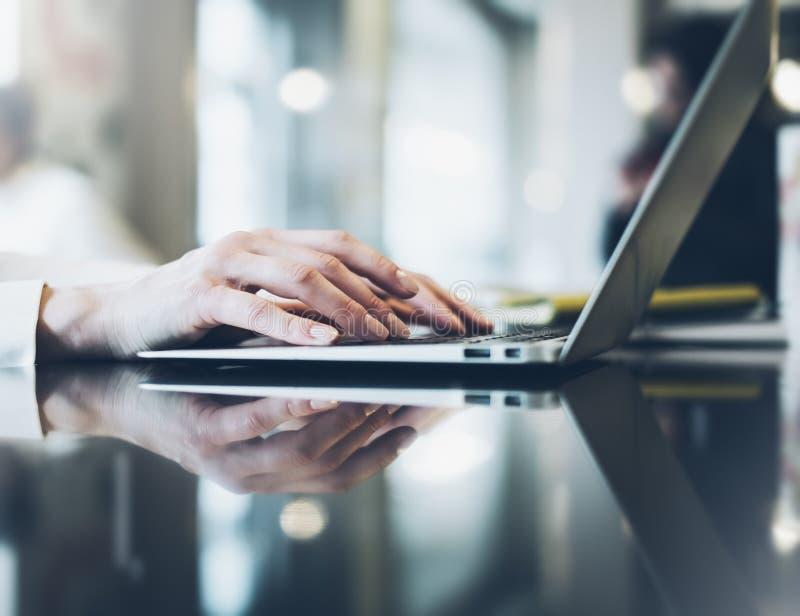 Mujer joven que escribe las manos de texto en el ordenador portátil abierto en un café en una tabla con resplandor de la reflexió fotos de archivo