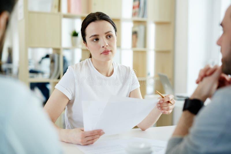 Mujer joven que escucha en la reunión con los clientes imagen de archivo