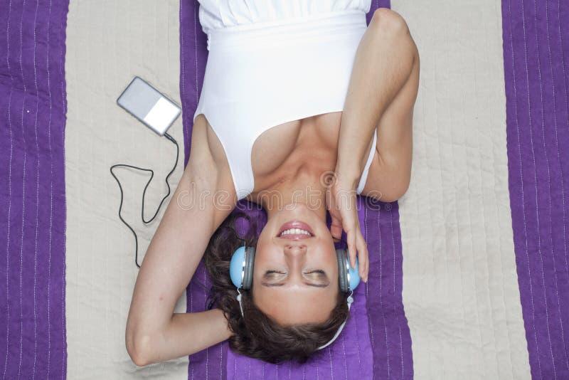 Mujer joven que escucha la música con reproductor Mp3 usando los auriculares mientras que miente en la manta de la comida campest foto de archivo libre de regalías