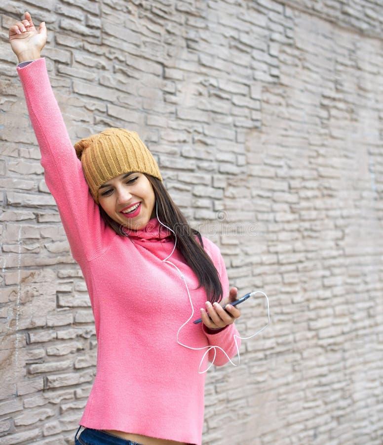 Mujer joven que escucha la música en auriculares y que baila en bric imagenes de archivo