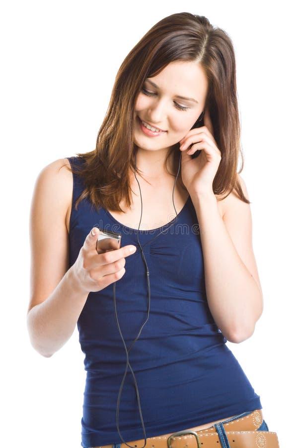 Mujer joven que escucha la música en el jugador mp3 foto de archivo libre de regalías