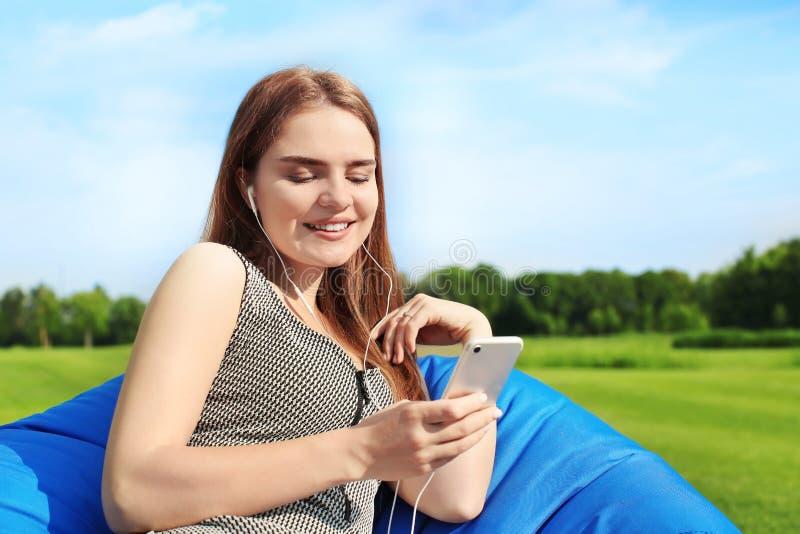 Mujer joven que escucha la música mientras que se sienta en silla del puf al aire libre fotografía de archivo